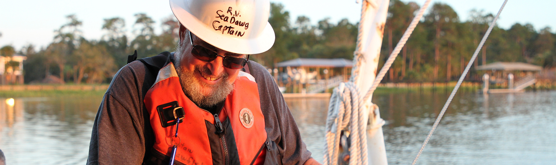 "John ""Crawfish"" Crawford wearing a hard hat and life jacket aboard a boat."