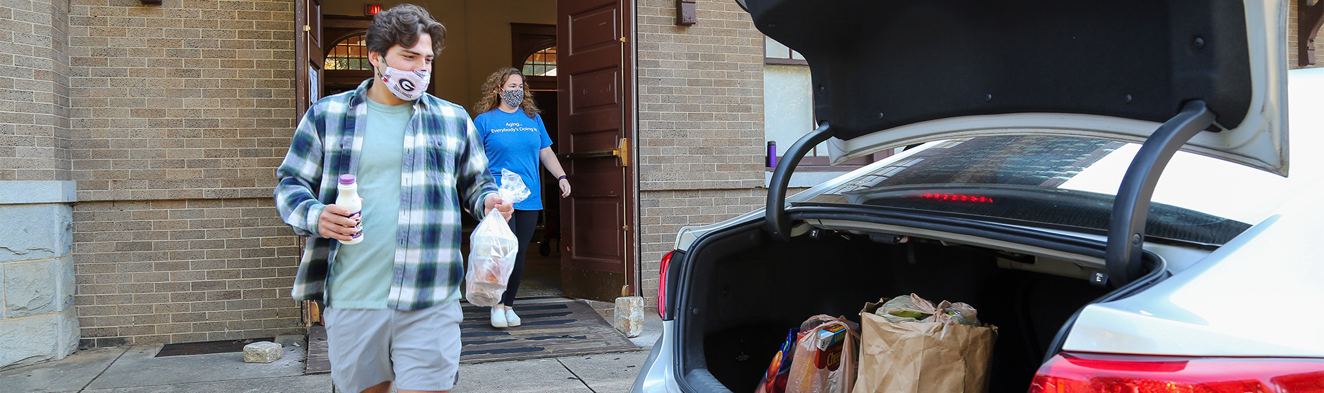 Volunteers load food into the back of a car