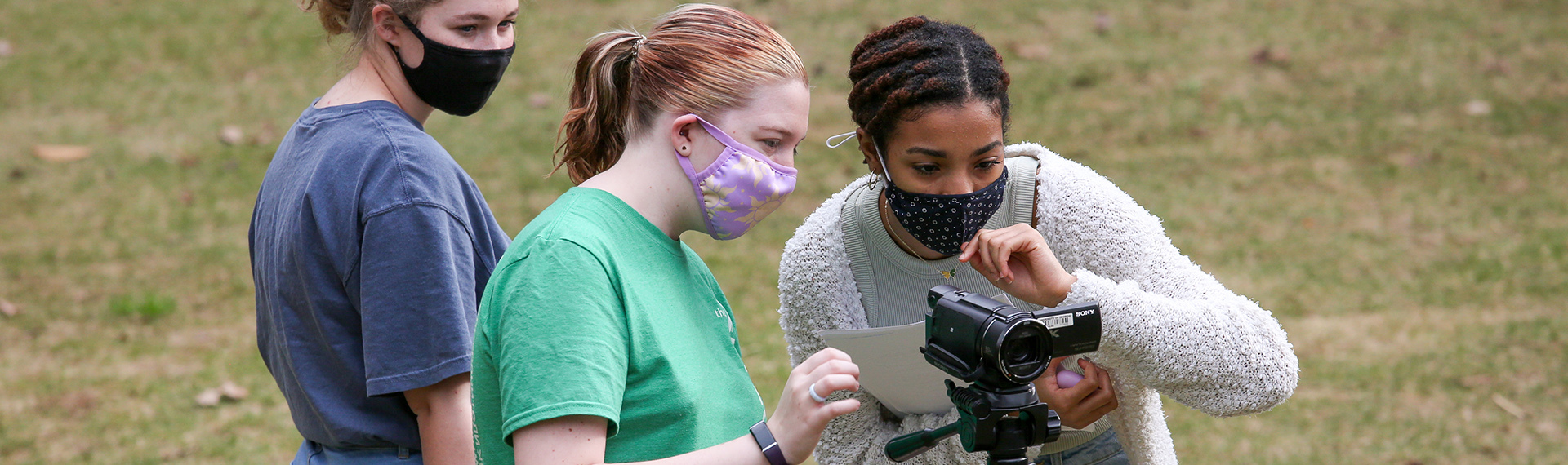 Three masked students look at a video camera on a tripod