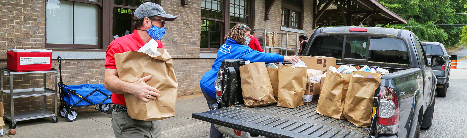 Volunteers load grocery bags of food into the back of a pickup truck.