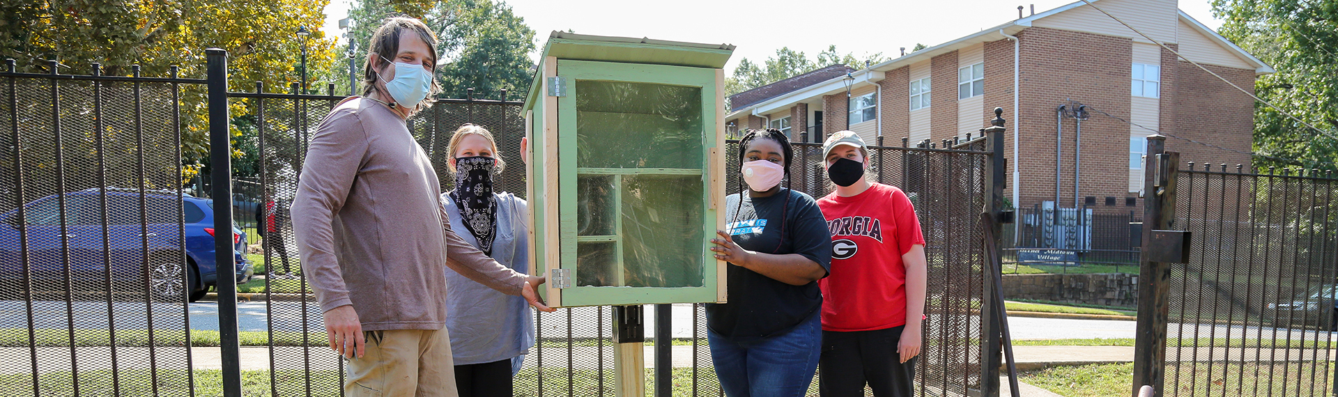 GIKI Coordinator Wick Prichard stands with Americorps VISTAs and Clarke County students next to a newly installed Little Free Pantry.