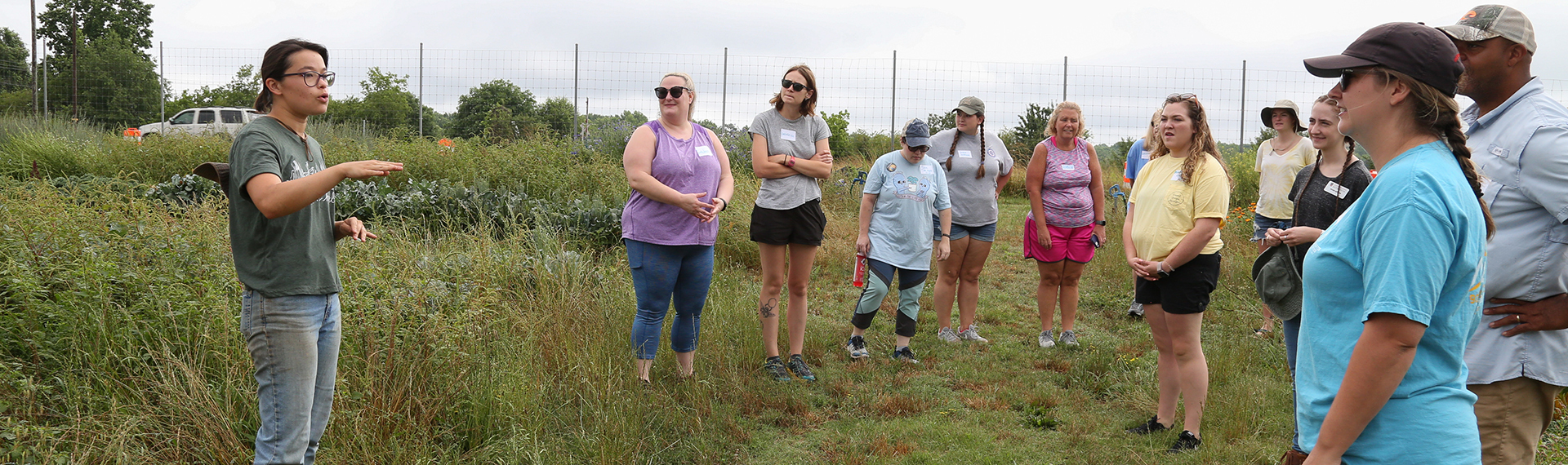 Teachers stand in a crop field at the UGArden learning about produce