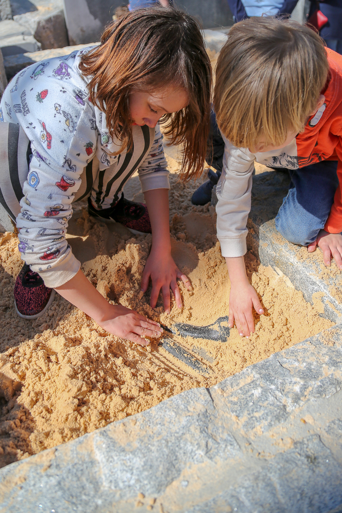 Digging for fossils in the sand pit.