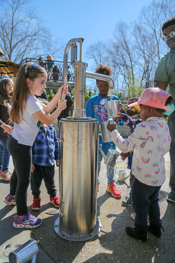 Kids pump water to take care of the plants in the dig and grow area.