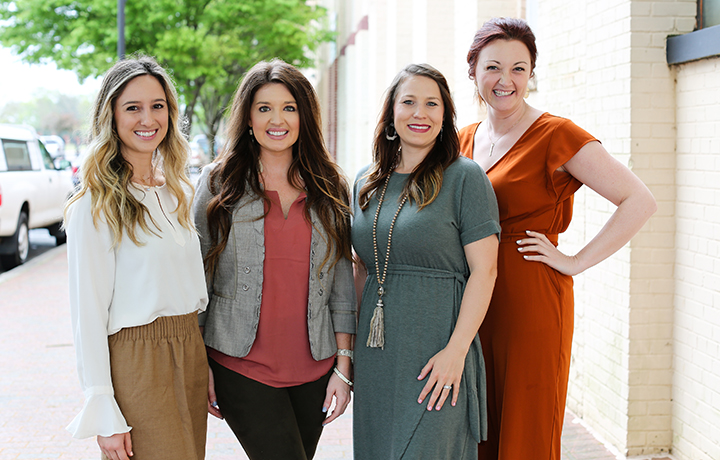 Lindsey Hogan, Alexandra Radford, Lauren Tatum and Rebekah Black smile in front of a white brick wall and sidewalk in downtown Buford