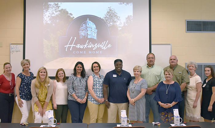 CVIOG and Archway staff pose with members of the steering committee revealing the new city of Hawkinsville logo