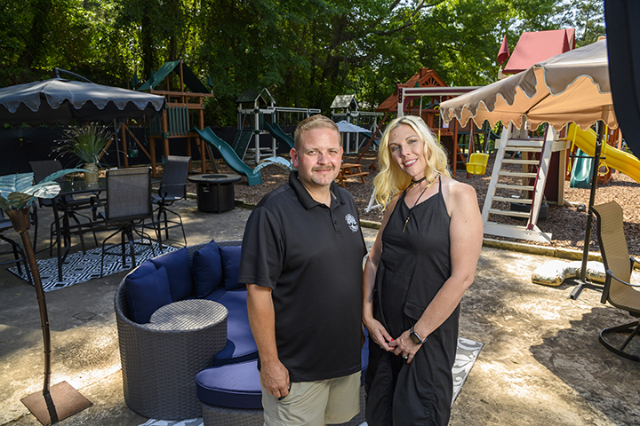 Joe and Sarah Bearden of Dreamscapes pose in front of playground equipment and other outside lawn furniture.