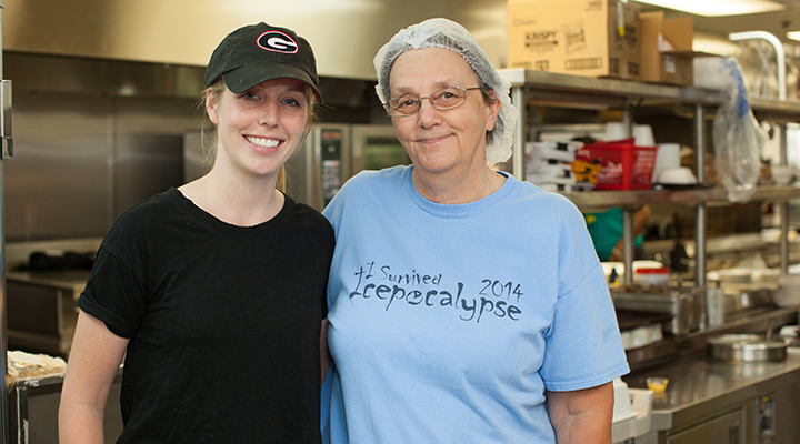 Sarah Jackson and a volunteer smile in front of a commercial kitchen.