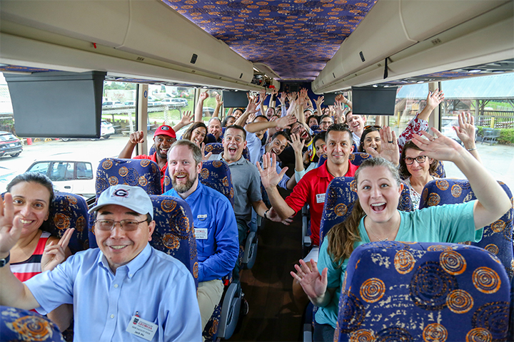 Members of the 2019 New Faculty Tour wave on the bus
