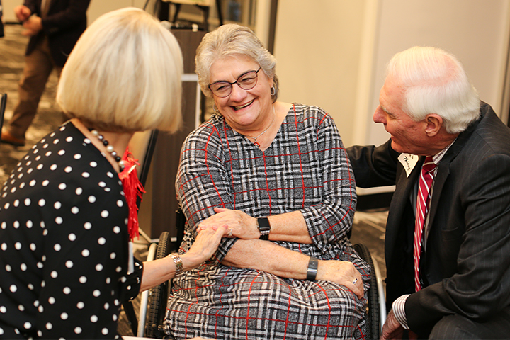 Louise Hill talks with guests at her retirement