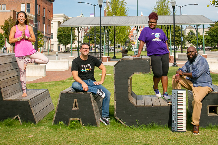 Local business owners Megan Carson, Scott Mitchell, Nora Stephens, and Anthony Howard pose on Macon sign