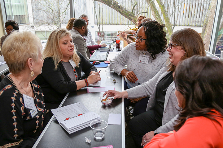 Attendees of the Community Leadership Conference sit and discuss topics at a table.