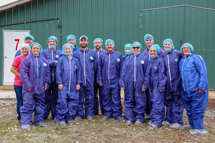 Students pose with their protective clothing outside the poultry facilities at JFK Farm.