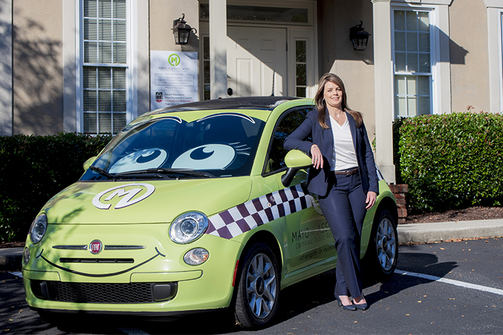 Lisa Mayo of Mayo & Associates poses with her custom company car