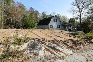 A dirt mound next to a house is evidence of a newly buried septic tank.