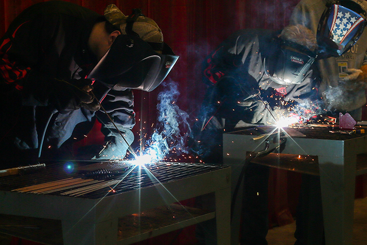 A pair of Thomson High School students welding