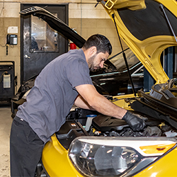 A mechanic works on a vehicle at ATC Auto Center