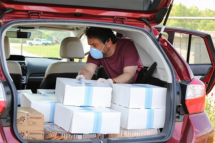 A volunteer wearing a protective face mask and gloves loads boxes of food into his car.