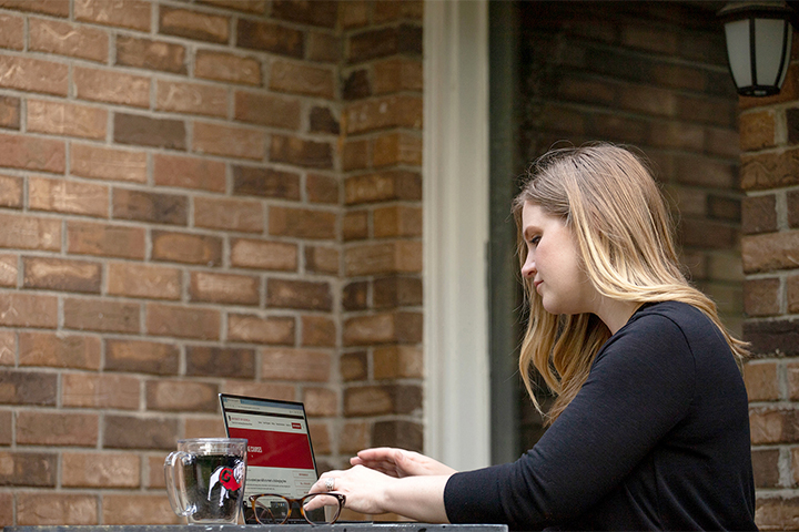 A woman works on her laptop at an outside table