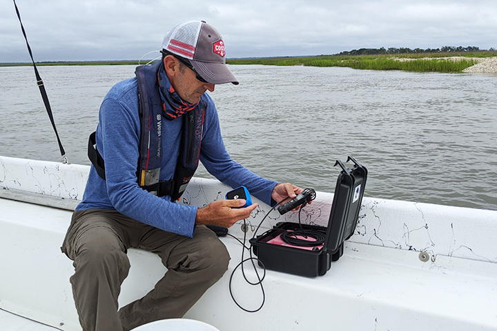 Todd Recicar using the hydrophone equipment to record underwater sounds.