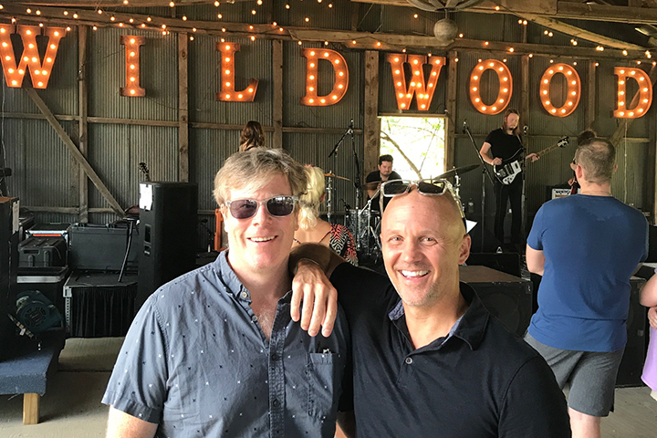 Team Clermont co-founders Nelson Wells and Bill Benson pose at a music venue.