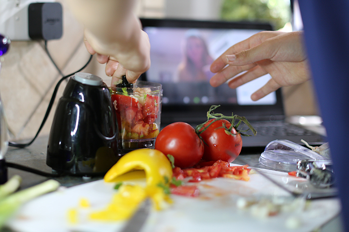 A closeup picture of a student's hands cutting produce while watching a video on a tablet.