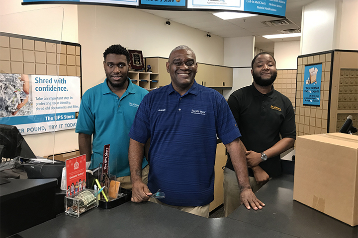 Joseph Malbrough poses with two employees inside his UPS store in Cobb County