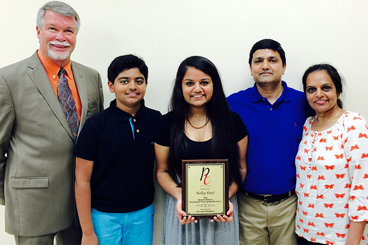 Helley Patel poses with four other people while holding an award.