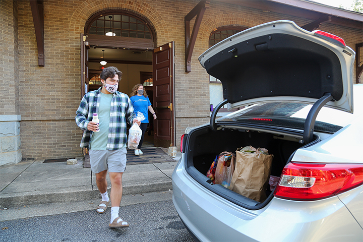 A student volunteer loads food into the back of a car.