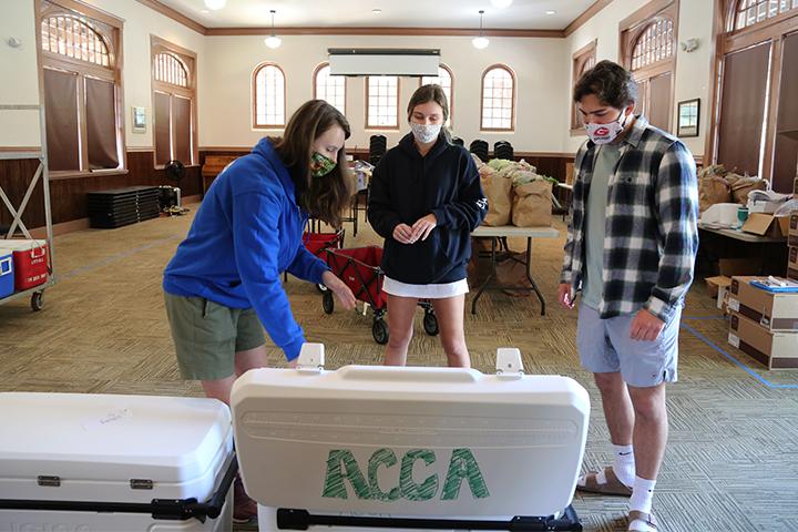 Three volunteers stand around a cooler.