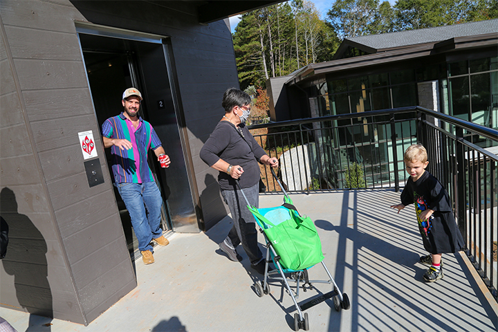 A man, a child, and woman pushing a stroller exit the outdoor elevator at the new entrance to the State Botanical Garden of Georgia.