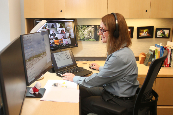 Tracy Arner sits at a desk in front of a computer while teaching an online continuing education course.