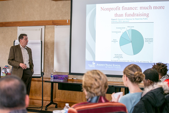 A man stands next to a projector screen showing information about nonprofit finance