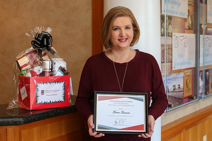 Karen Duncan poses with a framed certificate