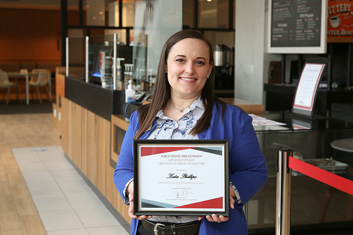 Katie Phillips holding a framed certificate of her Employee Spotlight Award