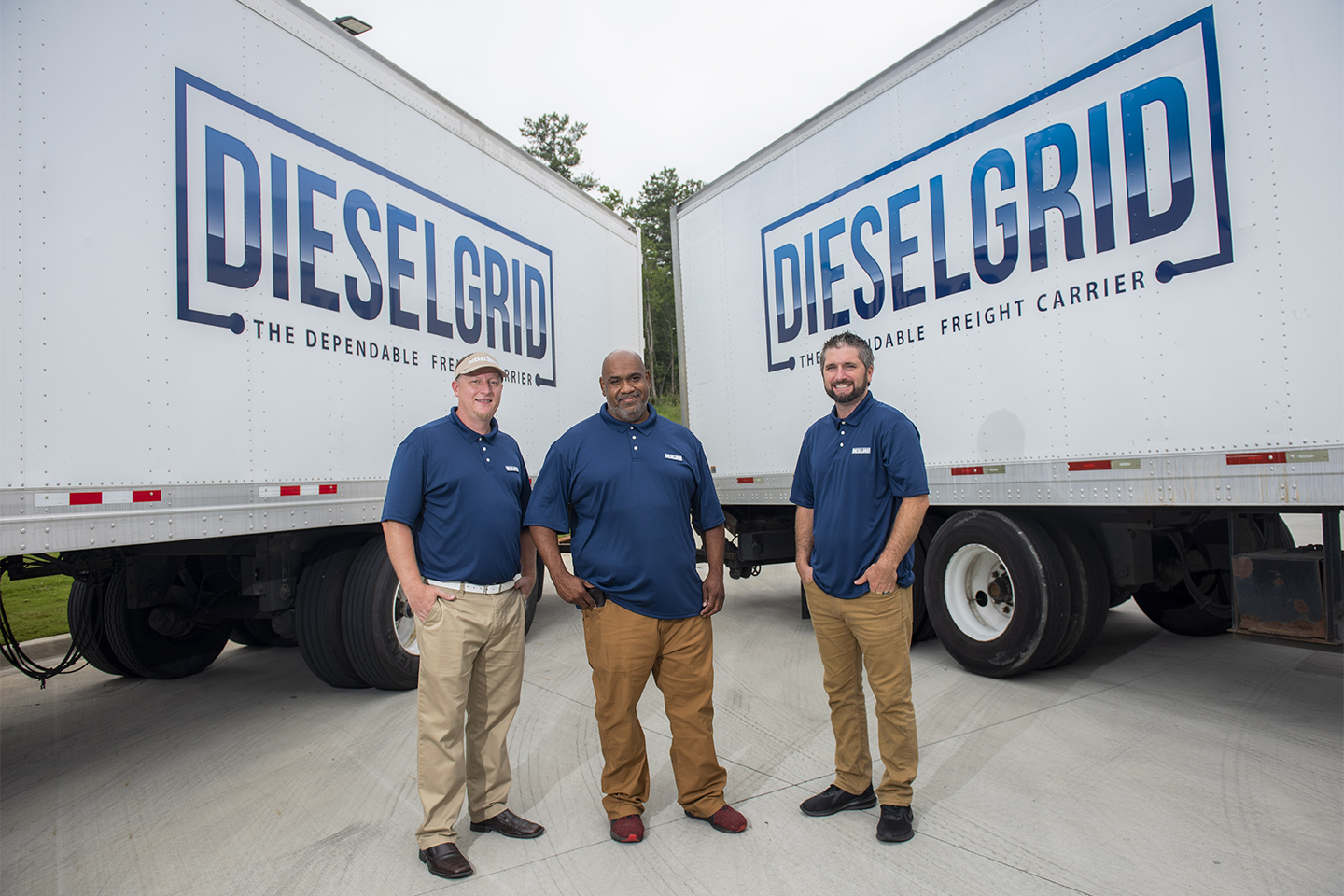 Three men stand in front of two semi-trucks with the DIESELGRID logo