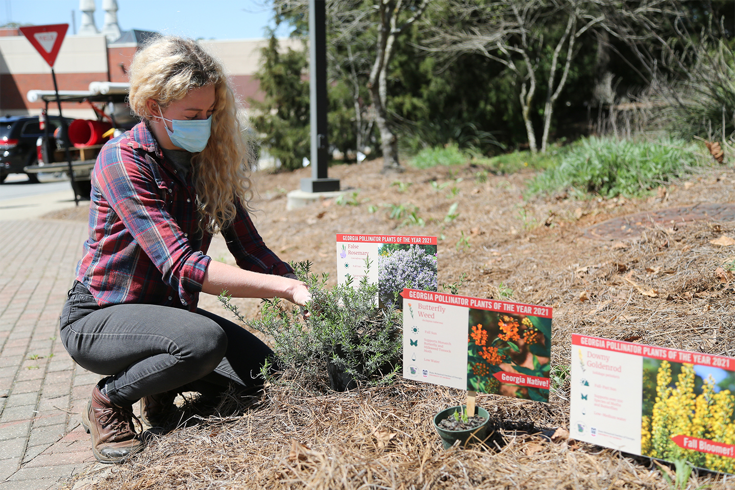 Lauren Muller kneels next to a plant bed with signs depicting pollinator plants