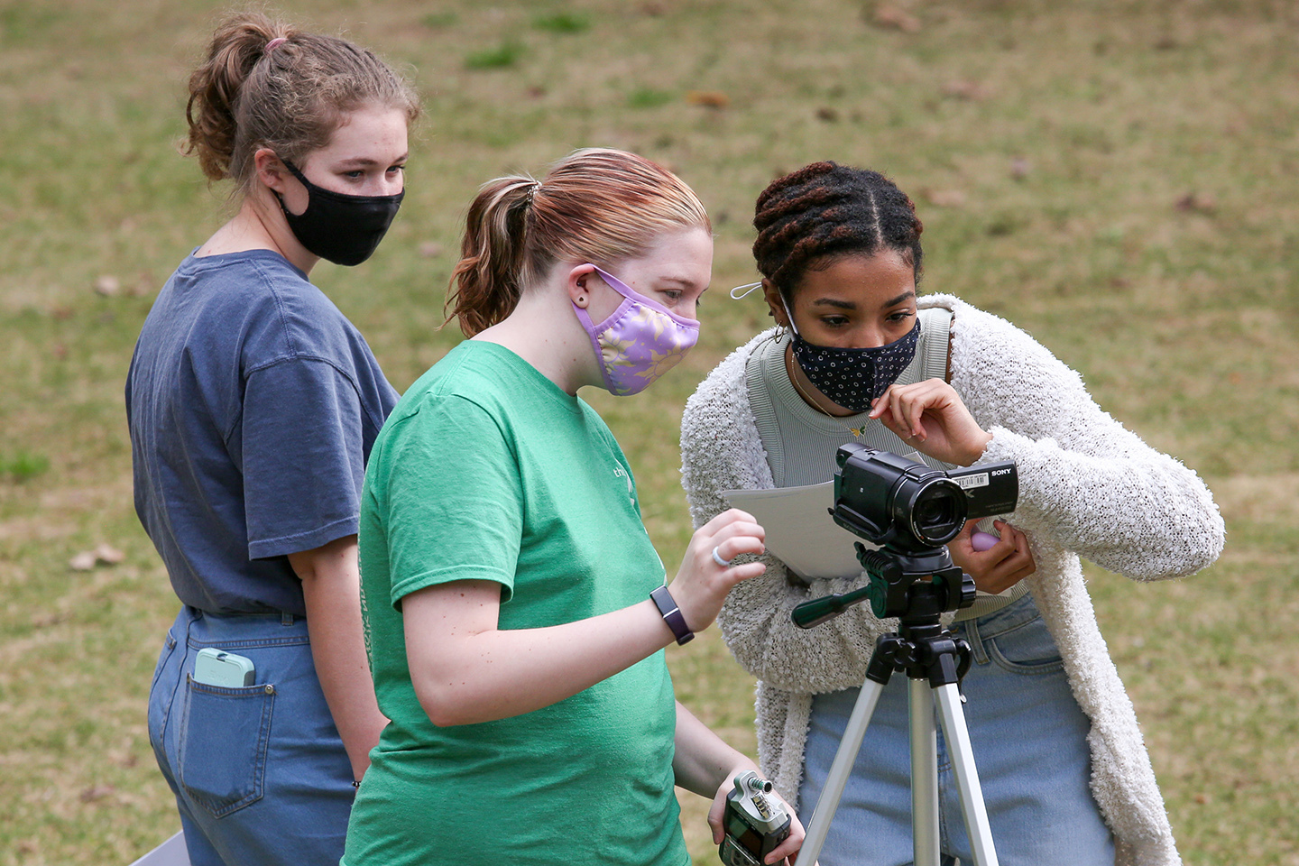 Three masked students looking at a video camera on a tripod