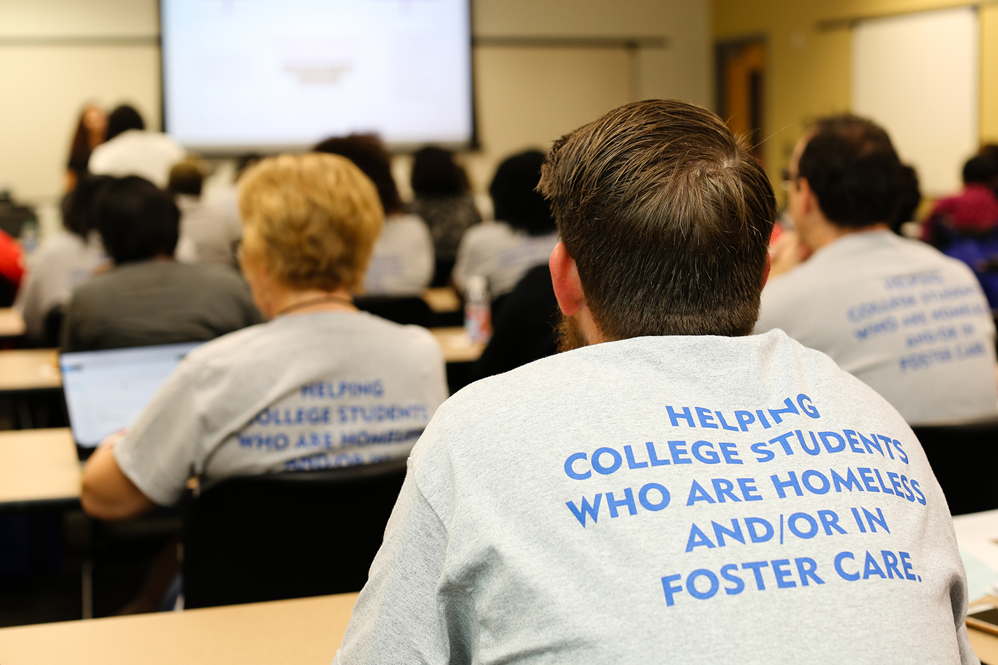 """A student sits in a classroom with an Embark Georgia shirt that reads """"Helping college students who are homeless and/or in foster care."""