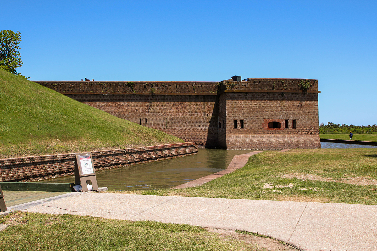 An outside wall of Fort Pulaski surrounded by a moat.