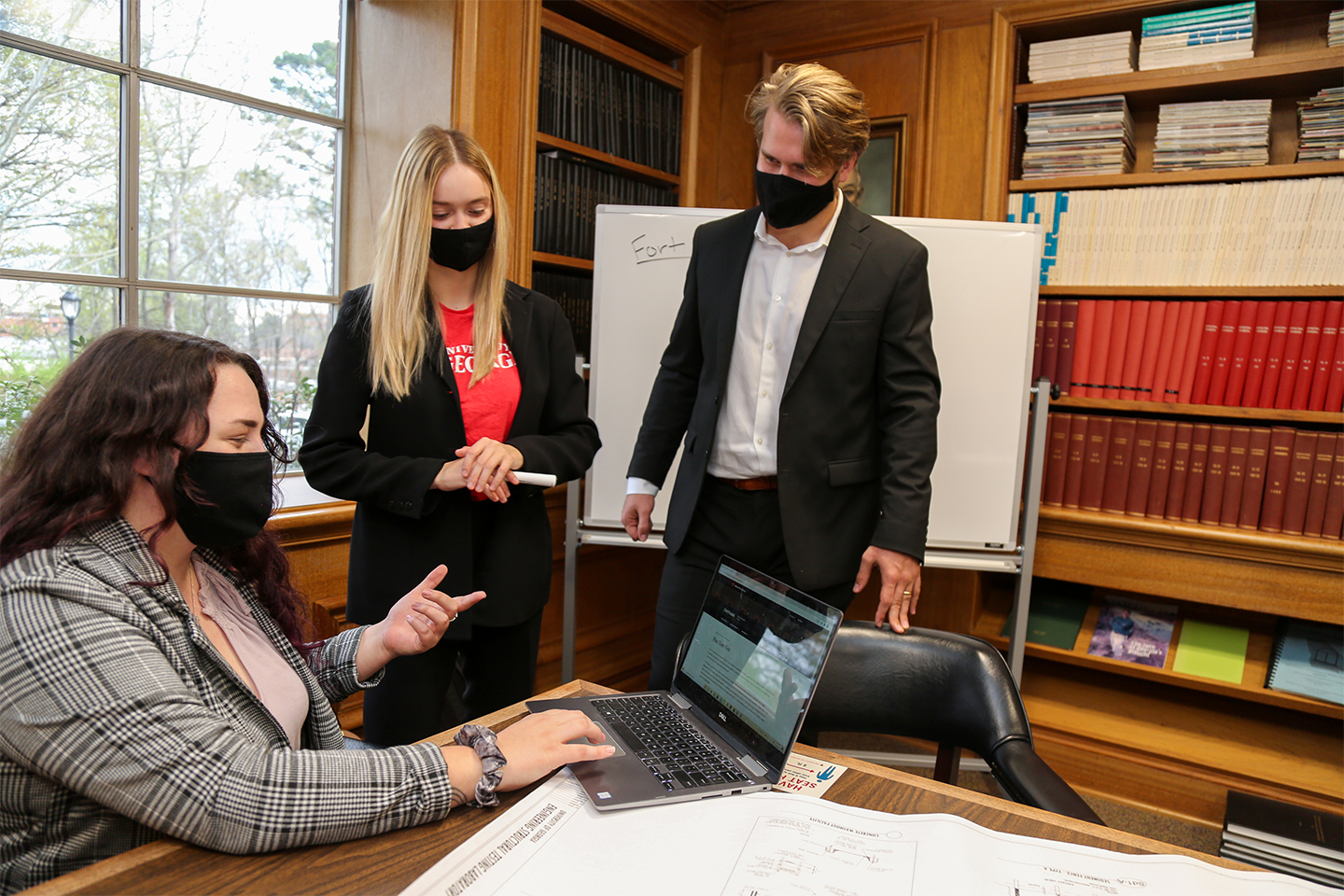 Three students wearing masks while working on a laptop
