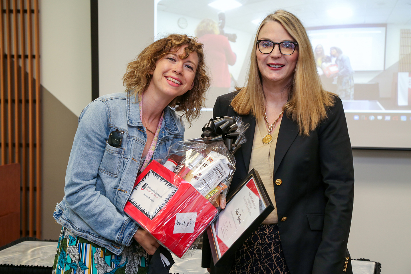 Natalie Stephens holds a gift basket and smiles next to Jennifer Frum