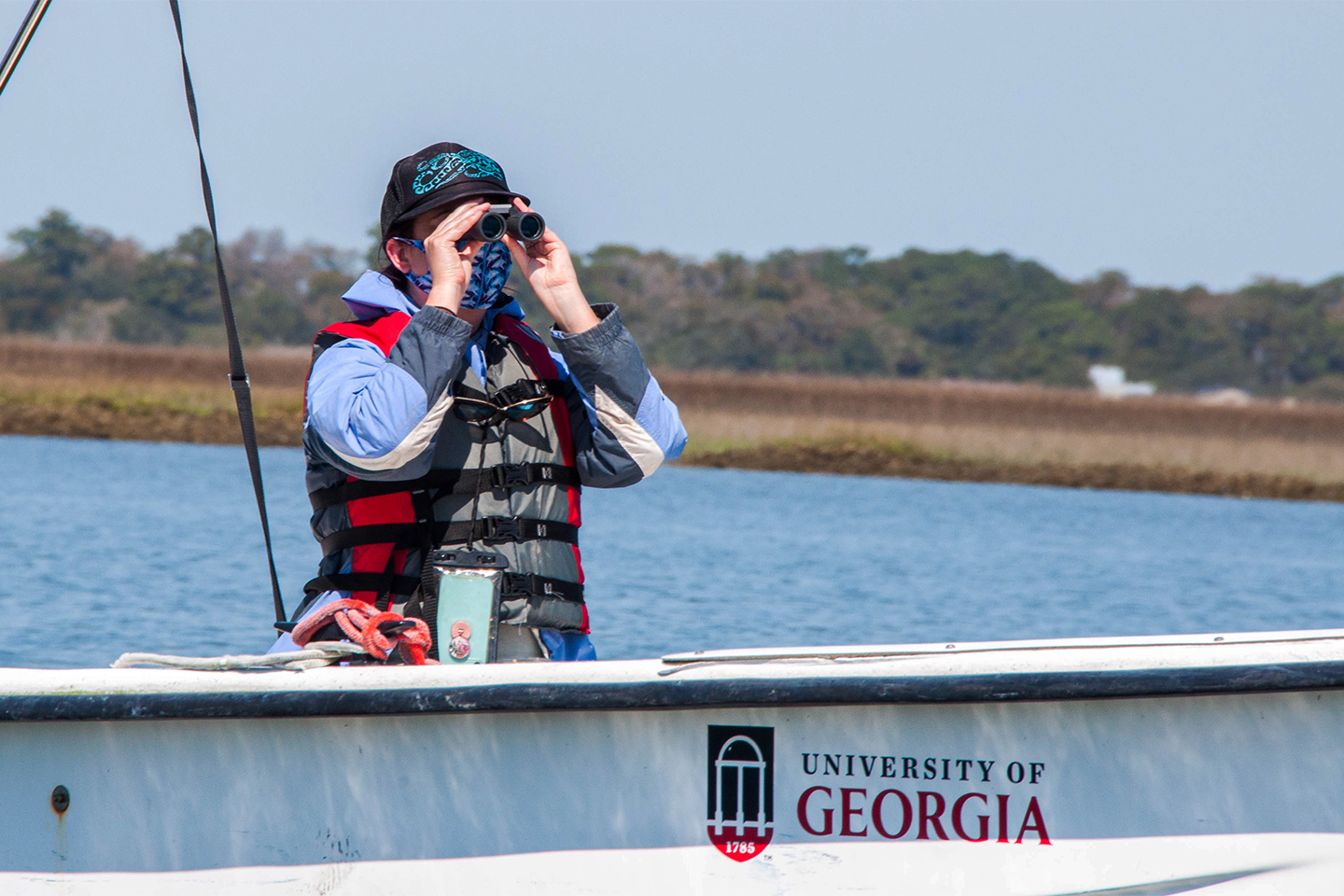 A person looks through binoculars on a boat