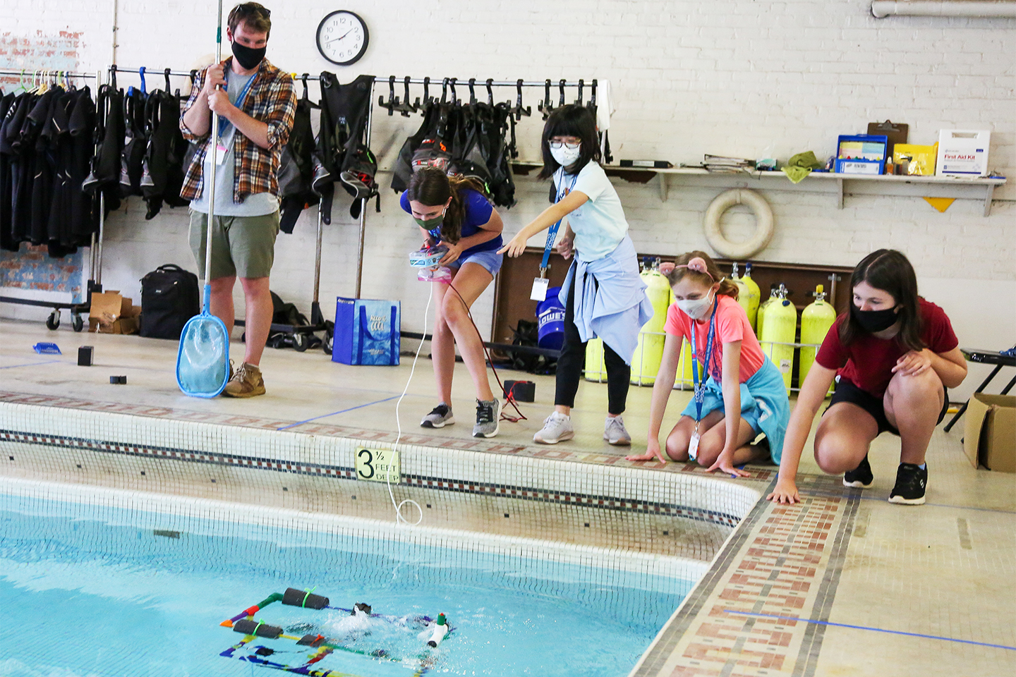 A group of students stand beside a pool while operating a robot in the water