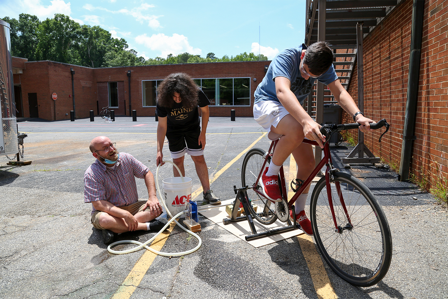A student rides a stationary bicycle attached to a water pump while two people watch