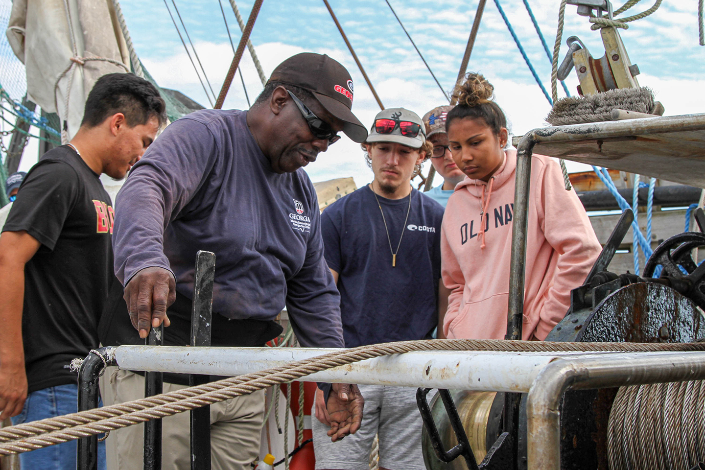 A teacher showing students a rope system on a boat