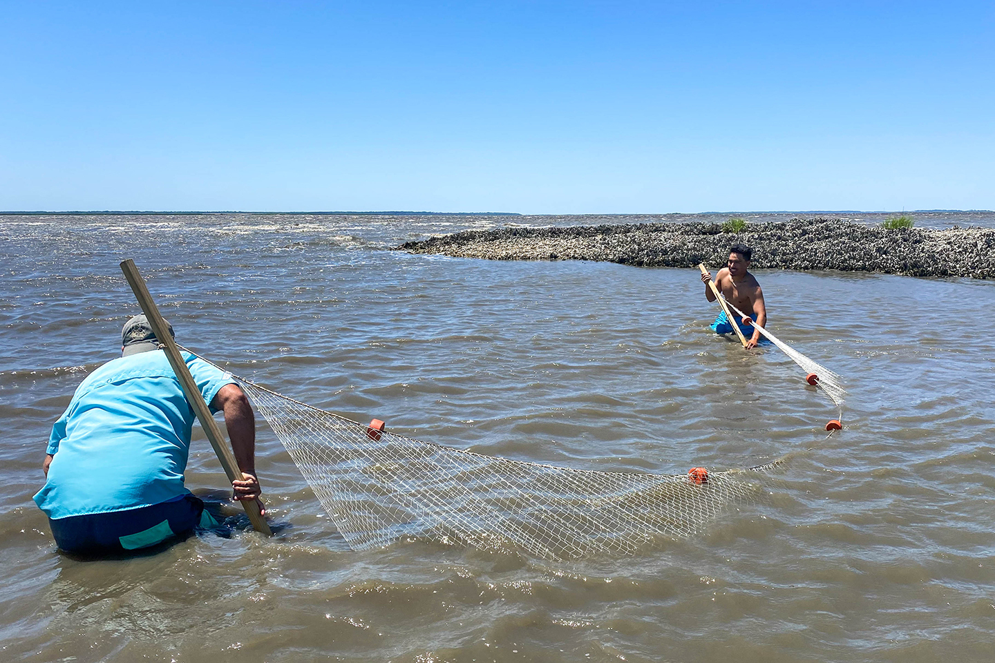 Two students stand in shallow water with a fishing net