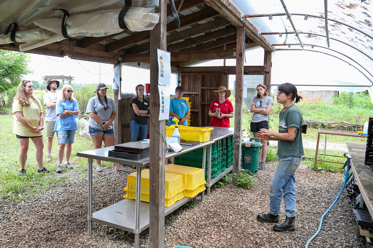 Teachers stand by a metal table under a shed while learning about produce