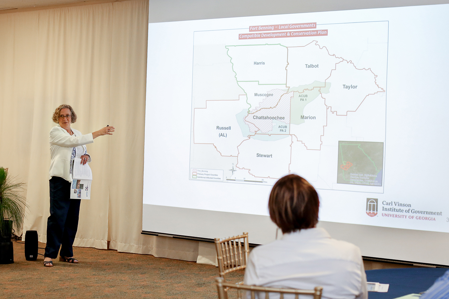 Saralyn Stafford speaks in front of a projector screen showing the ACUB territory.