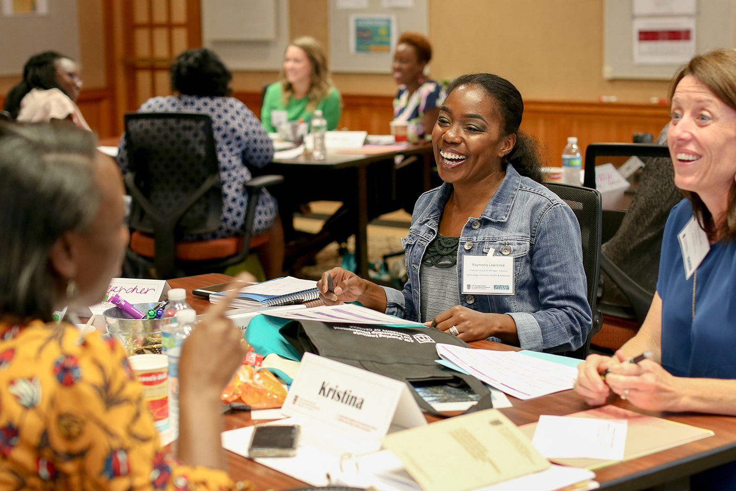 Women talk together at a table during a leadership session
